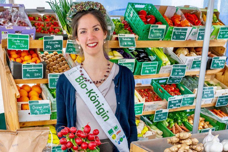 Biokönigin vor einem Gemüsestand mit Radieschen in der Hand.